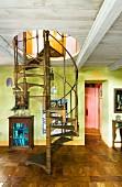 Wendeltreppe durch einfache Holzdecke in hellgrün getöntem Wohnraum