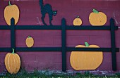 A Halloween Cut Out of a Black Cat on a Fence with Pumpkins