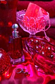 Still-life arrangement in red - perfume bottle next to various glass dishes on red satin cloth