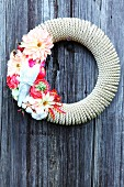 Love-themed decorative wreath made of coiled rope and flowers on wooden wall