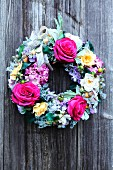 Wreath of flowers and ribbons on wooden wall