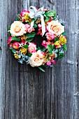 Dekokranz mit verschiedenen Blumenblüten und Schleife an Holzwand