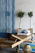 Wooden lounger in front of small trees in rattan planters