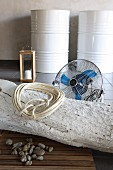 Coiled rope on whitewashed tree trunk on floor in front of fan with white-painted metal drums in background