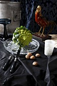 Romanesco cauliflower on crystal platter and black fabric in front of mounted pheasant