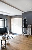 Geräumiger Eingangsbereich mit Garderobenständer und silberfarbenen Laternenleuchten auf Landhausdielen
