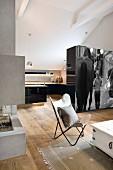 Offenes Wohnen im hellen Dachgeschoss mit Landhausdielen und moderner Designer Feuerstelle; Raumteilerschrank mit Fotokunst