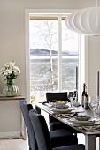 Dunkelblaue Polsterstühle an einer festlich gedeckten Tafel vor Fenstertür mit Blick auf die norwegische Schärenküste