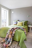 Classic lamp on side table next to bed with lime green throw and blanket with graphic pattern