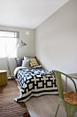 Metal standard lamp over bed with textiles in graphic patterns and olive green, vintage metal chair in foreground chair