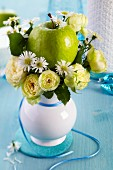 Vase of Blanchette roses, chamomile and a green apple