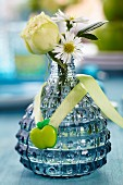 Rose and chamomile flowers in small blue vase decorated with apple-shaped button