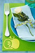 Place setting with rose and ribbon on green placemat with iron-on apple
