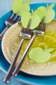 Cake forks on plate decorated with paper apples