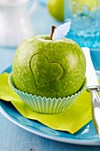 Green apple carved with love heart in cake case on plate