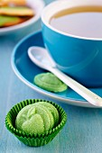 Green sweets with reliefs of apples in paper sweet cases in front of cup of tea