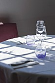 Light falling through window onto restaurant table set with cutlery and glasses