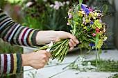 Floristenhände beim Kürzen der Stengel eines sommerlichen Blumenstrausses