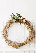Simple wreath of branches on a white plank wall