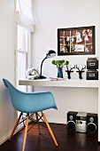 White desk, black accessories, floor-level window and sky blue, 50s retro shell chair