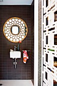 Tiny sink and ornamental round mirror on brown strip tiles accessorised with floral towel