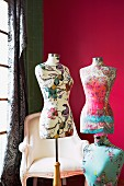Tailors' dummies covered in floral fabrics against deep pink background