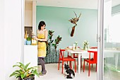 Red chairs at white table in dining room with pastel turquoise wall; counter, woman and dog to one side