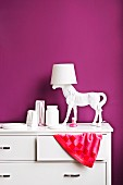 Accessories in girl's bedroom painted purple - horse lamp base on chest of drawers with edge of towel peeking out of drawer