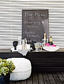 Improvised bar with glasses and bottles on dark wooden bench, menu written on chalkboard leaning on white slatted wall