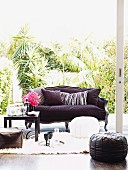 Sofa with purple cover, pouffes and floor cushions; drinks on black coffee table on white flokati rug