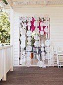 Curtain of doilies on strings on wooden veranda