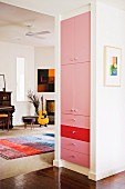 White cupboard with fronts painted pink and red; piano, guitar and brightly striped rug in music area in background