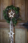 Wreath of Thuja twigs with birch bark star in centre and ribbons hung on rustic wooden door