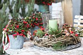 Plants with red berries in small metal buckets and candle lantern in willow wreath