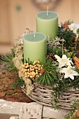 Rustic Advent arrangement with green candles in wicker basket