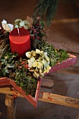 Wintry arrangement of red candle and natural materials in wooden star