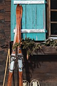 Vintage skis leaning against facade of cabin with turquoise window shutter