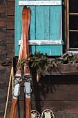 Vintage Skier an Hüttenwand und türkisfarbenem Fensterladen gelehnt