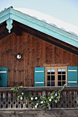 Snow on mountain cabin with turquoise shutters and ornate barge boards; nostalgic, knitted Christmas decorations on rustic balcony balustrade