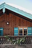 Schnee auf Berghütte mit türkisfarbenen Fensterläden und Ortgangbrett, nostalgische, gestrickte Weihnachtsdeko am rustikalen Balkongeländer