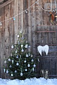 Decorated Christmas tree with hand-knitted baubles and angel's wings on facade of rustic wooden cabin in snow