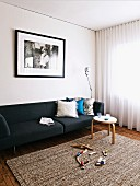 Toys on rug in front of black sofa below photo on wall and round side table in front of transparent curtains on window