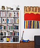 White bookcase with square divisions next to child's scooter and modern, colourful artwork on wall (Aboriginal art)