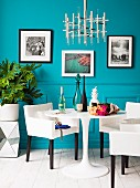 Replica designer lamp above small dining set; framed art prints on turquoise wall