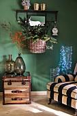 Sessel mit gestreiftem Bezug, Glasgefässe mit Lichterkette, Beistelltisch mit Ballonflaschen und Korb mit Weihnachtsdeko vor grüner Wand