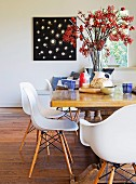 White shell chairs with wooden frames at rustic table, breakfast place settings around huge vase of berries and black and white picture in background