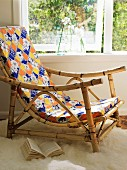 Armchair with bamboo frame and colourful patterned upholstery below window