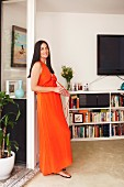 Woman wearing long orange dress leading on terrace door frame in front of half-height white bookcases below wall-mounted TV