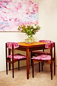 Wooden chair with patterned fabric seats and backrests around bouquet on table below large picture on wall