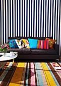 Mustermix - Streifenmuster auf Teppich und Wandbehang davor dunkelgraues Sofa mit bunte Dekokissen